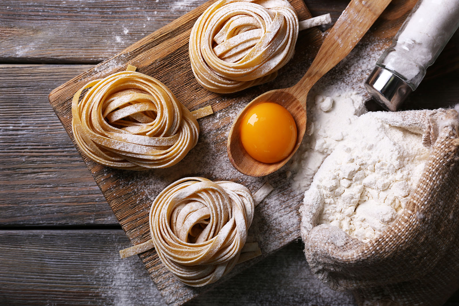 Raw homemade pasta and ingredients for pasta on wooden background; Shutterstock ID 260610080